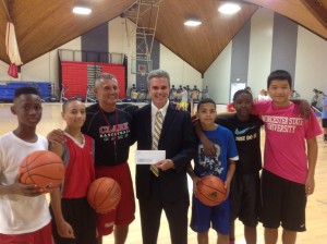 DA Early presents a check to Clark University men's basketball coach Paul Phillips. The money allowed inner-city children to attend the program.
