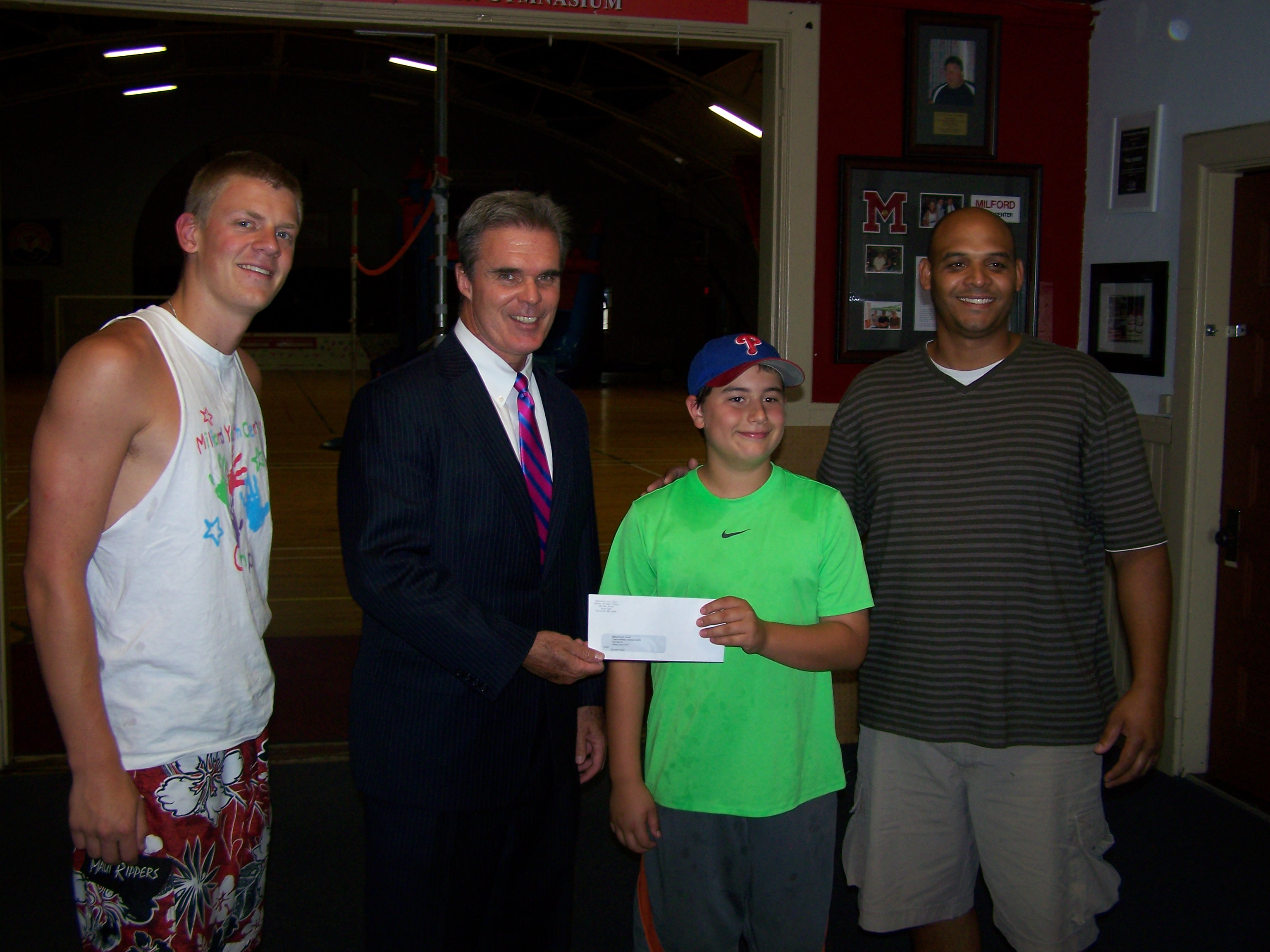 DA Early stands with Dan Seaver, Nick Wimette and Sidney De Jesus of the Milford Youth Center as he presents a check.