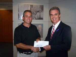 DA Early presents drug forfeiture funds to North High/Tech girls' soccer coach John Healey.