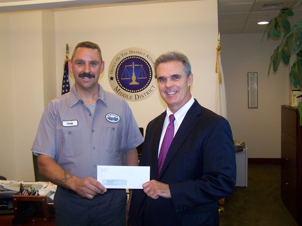DA Early presents a check to Craig Polewaczyk of Planting the Seed Foundation.