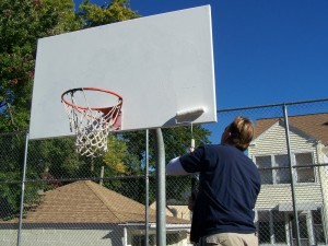 A Diversion Program employee paints a backboard at the Southbridge Community Center.