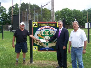 DA Early presents a check to groundskeeper John Gorman for improvements to Fuller Field in Clinton. George Oberg of the Fuller Field Commission looks on.