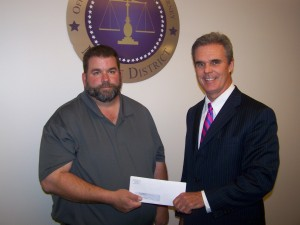 DA Early presents a check from drug forfeiture funds to John Todd of Tom Ash Little League.